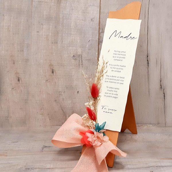 Poesía con Flores para la Madre. Poesía escrita en pergamino que se apoya sobre un atril de madera